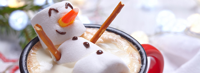 A smiling snowman made of marshmallows reclines in a mug of hot chocolate.