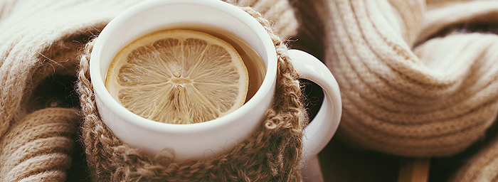 A hot mug of lemon tea is wrapped in a knitted cozy and nestled in a bundle of soft knitted fabric.