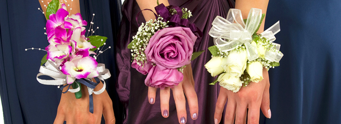 A close-cropped view of three women's wrists, each showing off a different corsage: the first with pink-tipped white orchids, the second with a dusty pink rose, and the third with white rosebuds.
