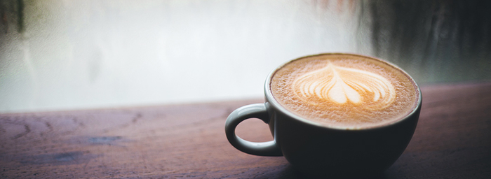 A cup of latte coffee sits on a wooden sill in front of a rain-spattered window.
