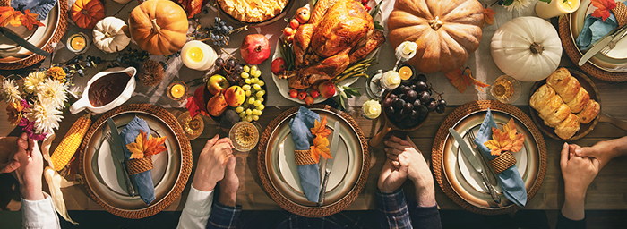 A view from above of a dinner table laid out with a massive Thanksgiving feast and places set around the table. At each place setting, a pair of hands is visible, and each person is holding hands with the people next to them.